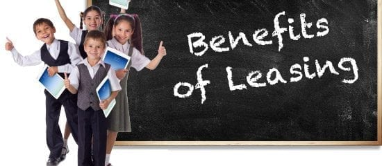 "Children using iPads next to a chalk board that reads ""Benefits of Leasing"""