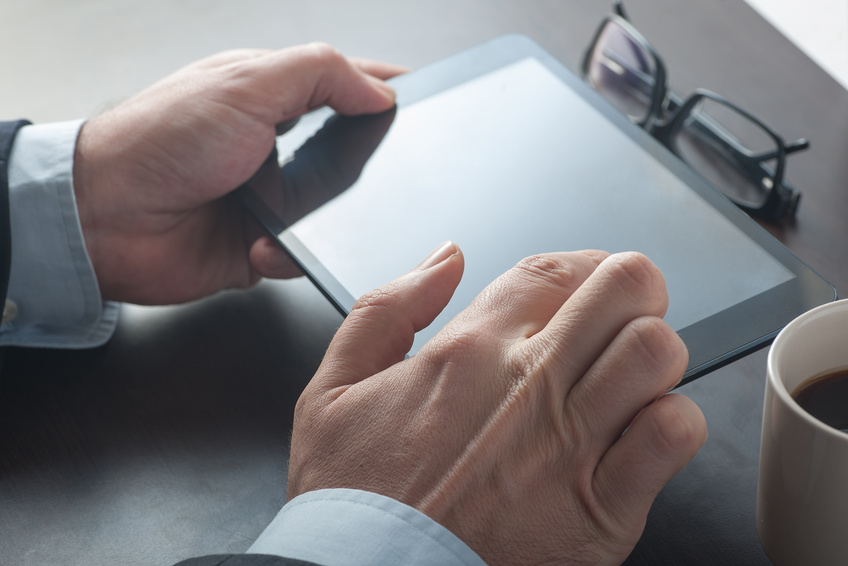 Businessman using a tablet device on his desk