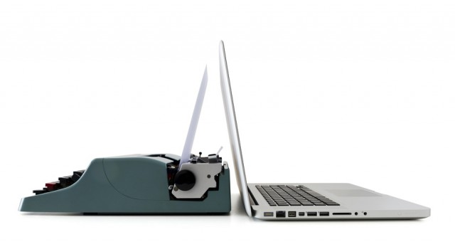 Laptop up against a typewriter