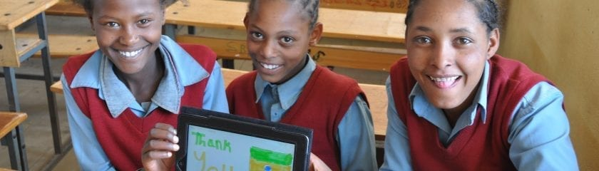 "Students at Bethany School in Ethiopia using an iPad with ""Thank you HardSoft"" written on the iPad"