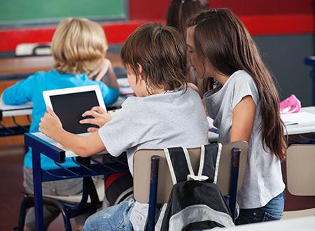Schoolchildren Using Digital Tablet In Classroom