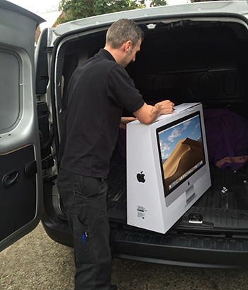 Engineer loading boxed iMac