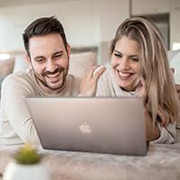 woman & a man huddled over MacBook