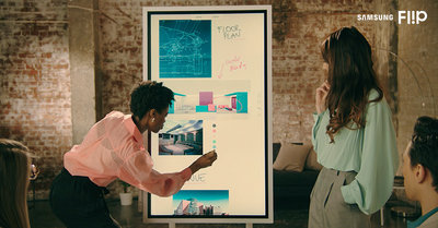 Meeting room with people surrounding a Samsung Flip. One woman is using the Samsung Flip Pen to select a colour to notate on the screen.
