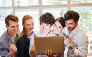 Group standing and looking at laptop