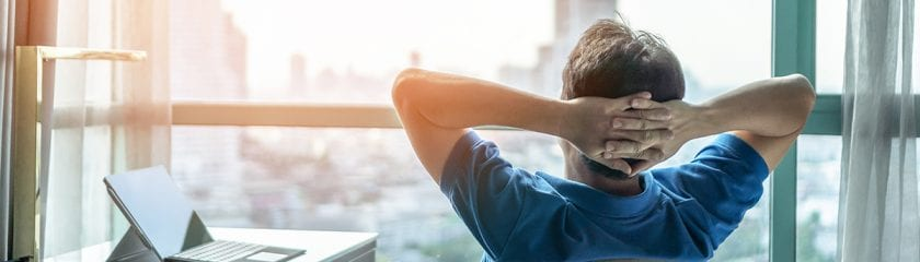 Man looking out of window with laptop next to him