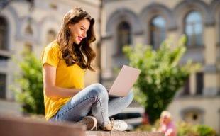 Lady wprking outside on a laptop