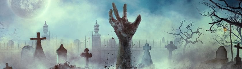 Zombie hand coming out of a grave in a graveyard in the dark
