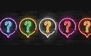 Neon light question marks in speech bubbles on a black brick wall background.