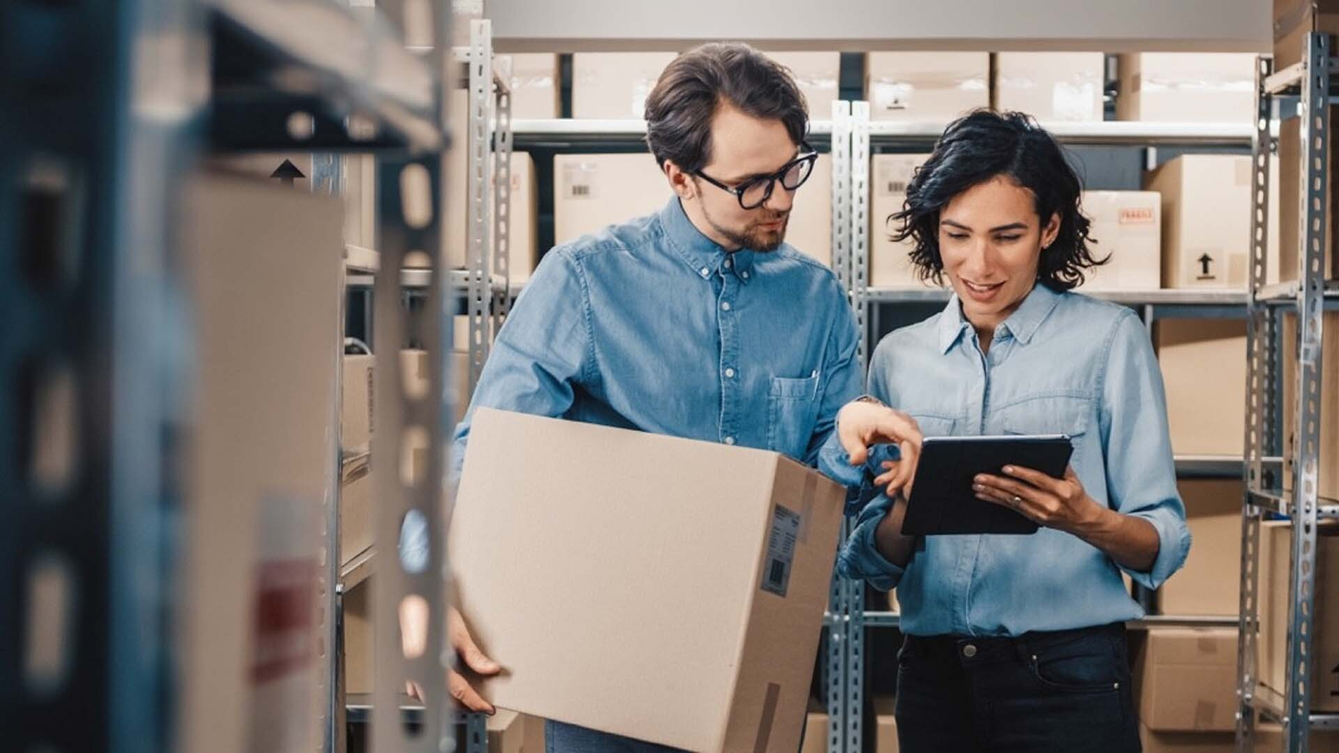 2 people standing in a warehouse with a tablet
